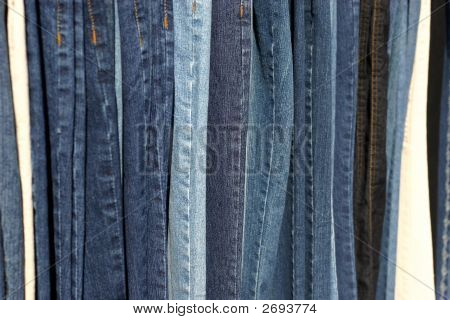 a row of different color blue jeans poster