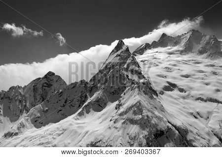 Black And White View From Ski Slope On Snowy Glacier And Mountain Peaks In Clouds. Caucasus Mountain