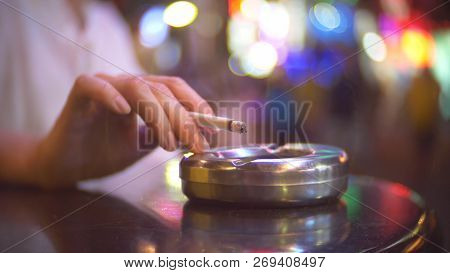 Close-up, Hand With A Cigarette Shakes Ash Into An Ashtray. A Single Woman Sits In A Cafe Outside Th