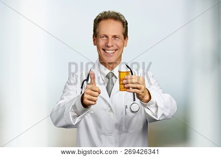 Cheerful Male Doctor Showing Thumb Up. Mature Medical Professional Holding Pills And Gesturing Thumb