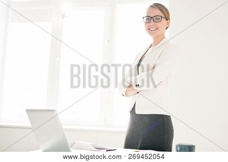Smiling Ambitious Female Lawyer In Eyeglass Standing At Table With Laptop And Looking At Camera Whil