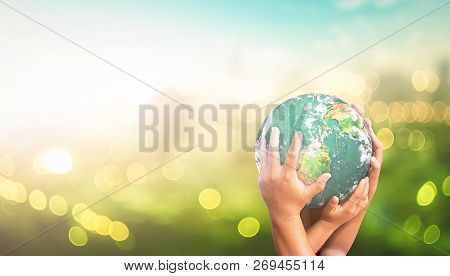 Community Care Concept: Human Hands Holding Earth Global Over Blurred Green City Background. Element