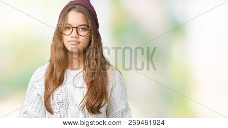 Young beautiful brunette hipster woman wearing glasses and winter hat over isolated background Relaxed with serious expression on face. Simple and natural looking at the camera.
