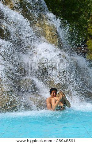 Mixed couple bathing near waterfall