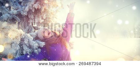 Winter Beauty Joyful Christmas Girl  having fun outdoors in winter park under the Christmas tree and laughing. Beautiful young woman celebrating Xmas and New Year. Enjoying nature, wintertime