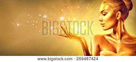 Gold Woman skin. Christmas magic gift. Beauty fashion model girl with Golden make-up, hair and jewellery on gold background. Holding Gold miracle in hand. Metallic glance Fashion art portrait, glamour