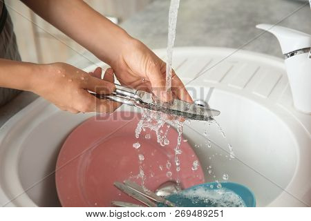Woman washing dishes in kitchen sink, closeup view. Cleaning chores poster