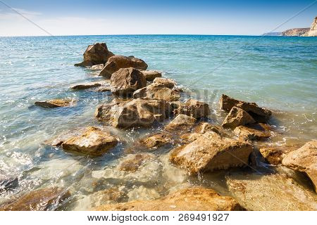 Blue Mediterranean Sea With The Sparkling Surface And Stones In Cyprus.