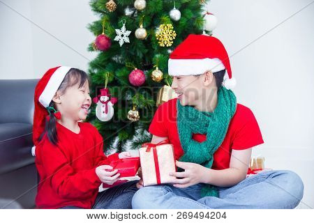 Young Asian Sibling,brother And Sister Holding Present Boxes And Smiling Together At Home With Chris