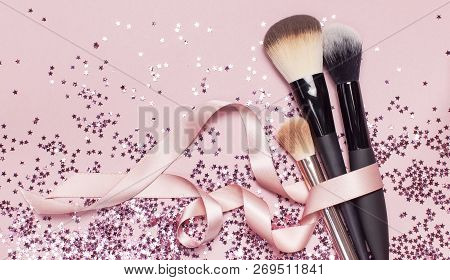 Different Cosmetic Makeup Brushes With Pink Ribbon And Holographic Glitter Confetti In The Form Of S