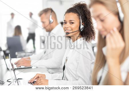 Call Center Worker Accompanied By Her Team. Smiling Customer Support Operator At Work. Young Employe