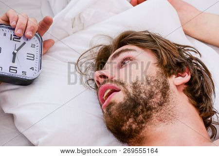 Handsome Man Using Clock In Bed After Waking Up In The Morning. Lazy Man Happy Waking Up In The Bed