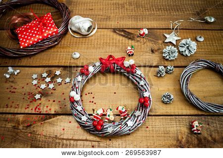 Hand Made Christmas Wreaths And Packaging Christmas Gifts On Dark Wooden Background Top View.