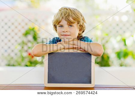 Happy Little Kid Boy With Chalk Desk In Hands. Healthy Adorable Child Outdoors Empty Desk For Copysp
