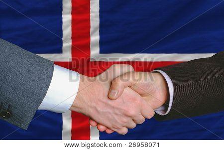 Businessmen Handshake After Good Deal In Front Of Iceland Flag