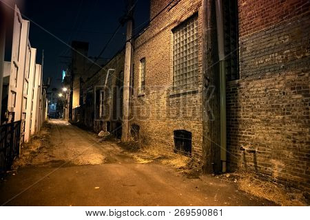 Dark and scary urban city alley with a vintage brick a wall at night
