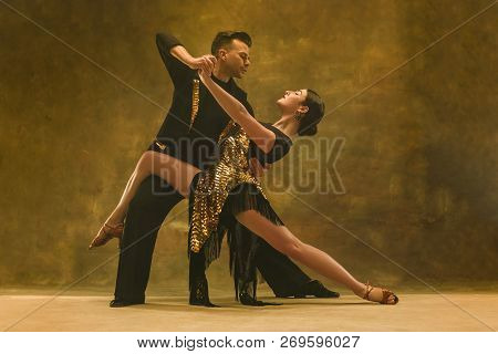 The Young Dance Ballroom Couple In Gold Dress Dancing In Sensual Pose On Studio Background. Professi