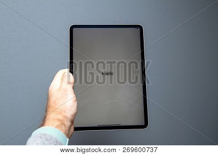 Paris, France - Nov 14, 2018: Man Holding The New Ipad Pro Tablet By Apple Computers Against Gray Ba
