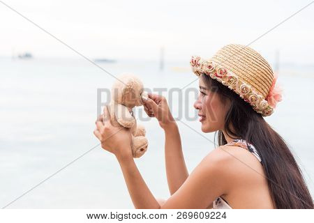 Asian girl in white dress sitting on the beach Tease with teddy bear with love nostalgia On vacation in summer. poster