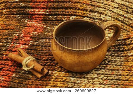 Exclusive ceramic tea cup and sticks of fragrant cinnamon knitted with thin jute twine on knitted soft melange background. poster