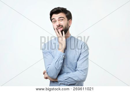 Young European Man In Blue Shirt Thinks, Looks Through Incredulously