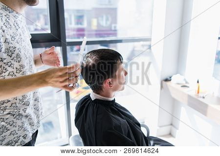 A professional hairstylist with a comb and scissors in his hand styling the wet black and short hair of the man in a hair salon poster