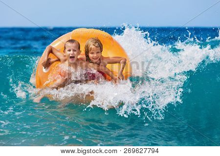Happy Kids Have Fun In Sea Surf On Beach. Joyful Couple Of Children On Inflatable Ring Ride On Break