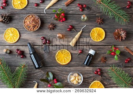 Bottles Of Essential Oil On A Wooden Christmas Background With Myrrh, Frankincense, Wintergreen Twig