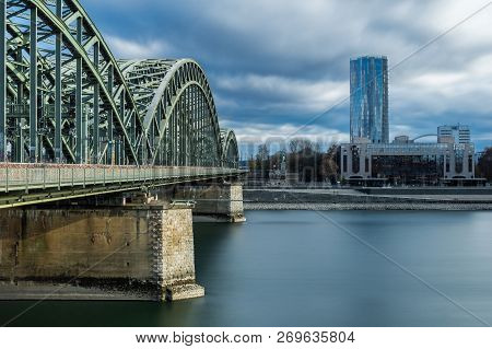 View Of The Hohenzollern Bridge, The Skyscraper Cologne Triangle And The Long River Rhine (one Of Th