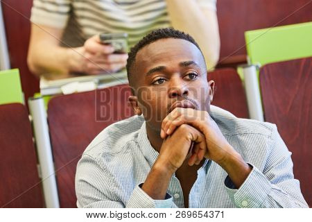African man as student thinking during university lecture