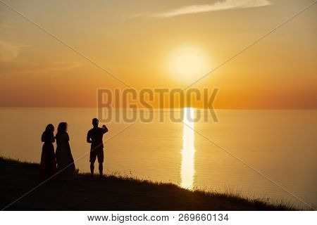Silhouettes of man and two women at seashore on sunset.
