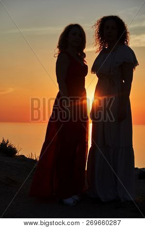 Two women in dresses stand at shoreline on sunset.