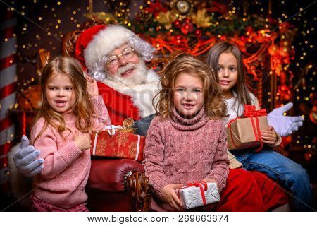 Happy children are sitting at home with Santa Claus. Miracle time. Christmas, New Year.