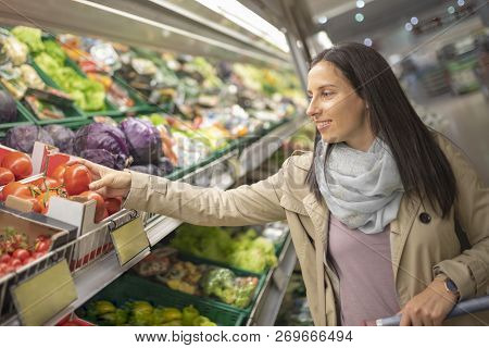 Pretty Young Woman Picking Up, Choosing Green Leafy Vegetables In Grocery Store. Attractive Woman Sh