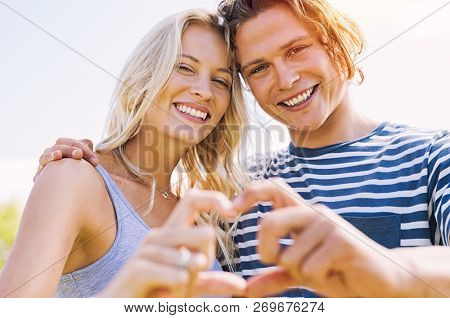 Closeup of young man and beautiful woman making heart shape with hands. Portrait of loving couple making heart shape with hands at park and looking at camera. Romantic girlfriend and boyfriend in love