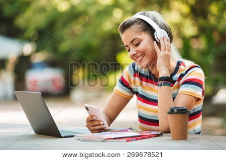 Happy young teenage girl listening to music with headphoes, studying with laptop at the park