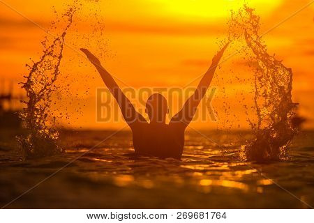 A Man In The Tropical Sea Raises The Spray With A Wave Of His Hands. Silhouette Photo. Golden Colorf