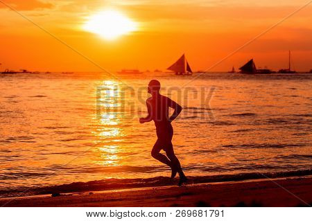 A Man On A Run On A Tropical Beach. Silhouette Photo On The Background Of A Golden Colorful Sunset.