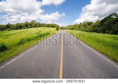 Highway Road Up Hill Through Green Grass Field Under White Clouds On Blue Sky In Summer Day. Road Tr