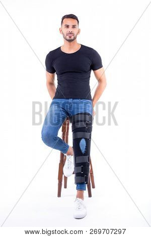 man wearing supportive leg brace in studio with white background