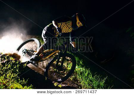 Professional DH Cyclist Riding the Mountain Bike on the Forest Trail at Night. Extreme Sport and Enduro Cycling Concept.