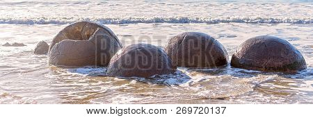 Large spherical Moeraki boulders exposed in the beach surf on the Otago cost of New Zealand poster