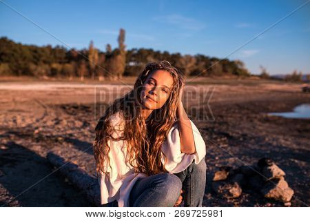 A Portrait Of A Beautiful Young Careless Woman Outdoor, Sunsets Lights Embracing Her Figure. Beautif