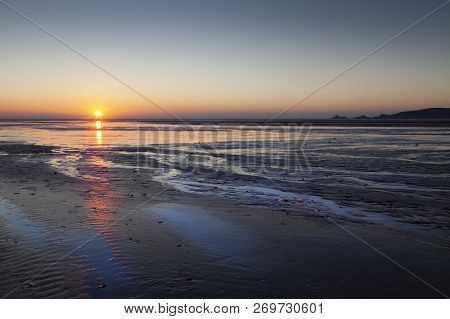Sunrise Over Swansea Bay On A Low Tide, Showing Mumbles Lighthouse And Pier, South Wales, Uk