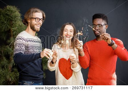 Young Friends In Sweaters Having Fun Together Celebrating New Year With Bengal Fire Indoors