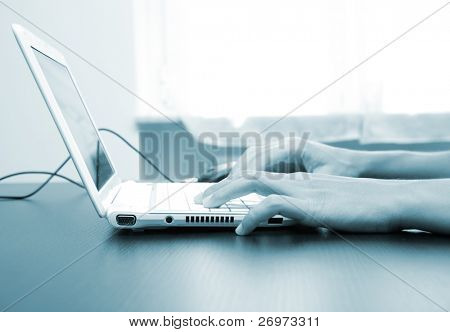 Blue toned image of male hand typing on a computer keyboard