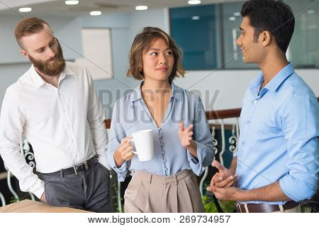 Business Colleagues Discussing Work During Coffee Break. Group Of Coworkers Talking In Office Space,