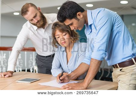 Creative Team Member Sharing Ideas With Two Colleagues. Indian Office Employee Drawing On Paper, Whi
