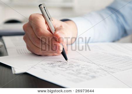 Closeup ein Geschäftsmann Hände beim Schreiben einige Dokumente