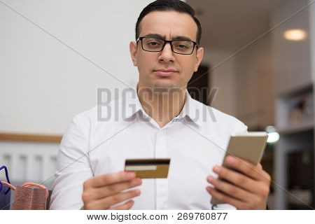 Portrait Of Serious Young Man Using Mobile App For Online Shop. Mixed Race Guy Wearing Glasses Doing